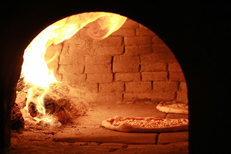 Cuisson des pizzas au feu de bois dans la Pizzeria Sicilia au bas de la rue du Pila Saint Gély au centre-ville de Montpellier (credits photos :EDV-Fabrice Chort)